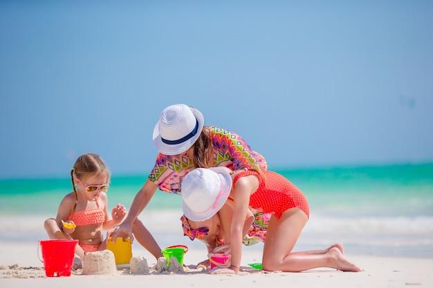 Matka i dwoje dzieci bawiące się piaskiem na tropikalnej plaży.