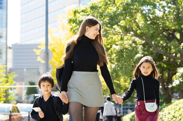 Matka i dwoje dzieci spacery na świeżym powietrzu, trzymając się za ręce z uśmiechem
