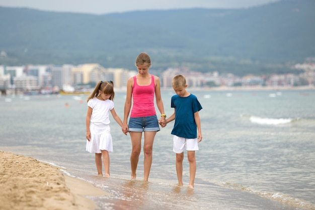 Matka i dwoje dzieci, syn i córka, chodzą razem na piaszczystej plaży w wodzie morskiej latem