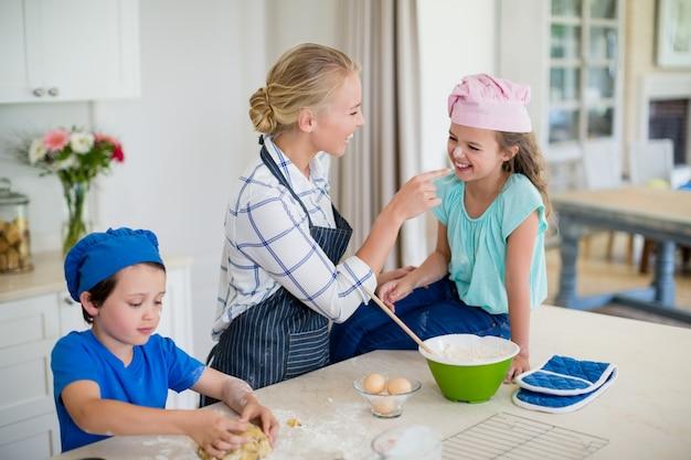Matka i dzieci bawią się podczas robienia ciasta w kuchni