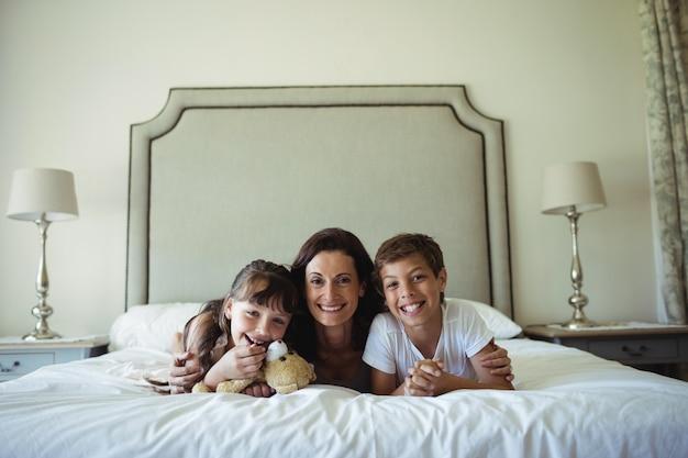 Matka i dzieci leżące na łóżku z misiem w sypialni