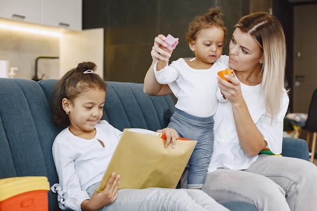 Matka i dzieci razem wypoczywają na kanapie w domu w salonie. małe dziewczynki czytają książkę i bawią się zabawkami.
