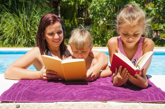 Matka i dzieci stojące w czytaniu basenów