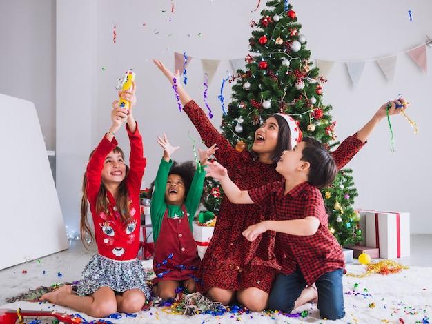 Matka i dzieci świętują boże narodzenie i bawią się i cieszą w domu z choinką