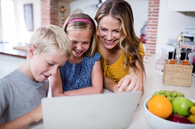 Matka i dzieci za pomocą laptopa w kuchni