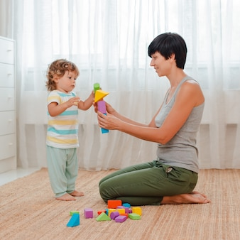 Matka i dziecko bawią się na podłodze w pokoju dziecinnym. mama i mały chłopiec budują wieżę z kolorowych klocków.