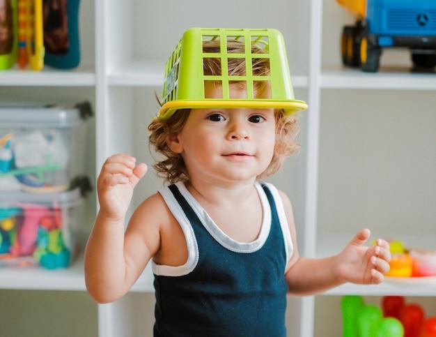 Matka i dziecko bawią się na podłodze w pokoju dziecinnym. mama i mały chłopiec robią z plastikowymi kolorowymi zabawkami.