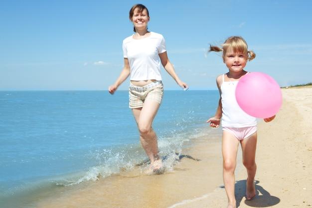 Matka i dziecko biegają po morskiej plaży