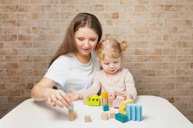 Matka i dziecko dziewczyna bawi się zabawkami blokowymi na białym stole