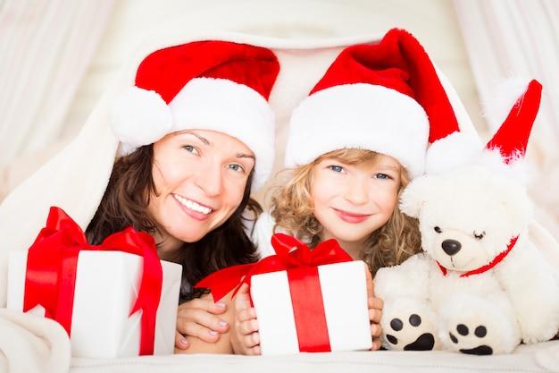 Matka i dziecko gospodarstwa pudełka na prezenty świąteczne. szczęśliwa rodzina w domu