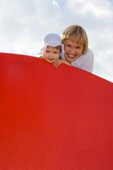 Matka i dziecko hald czerwony plakat nad niebem z chmurami