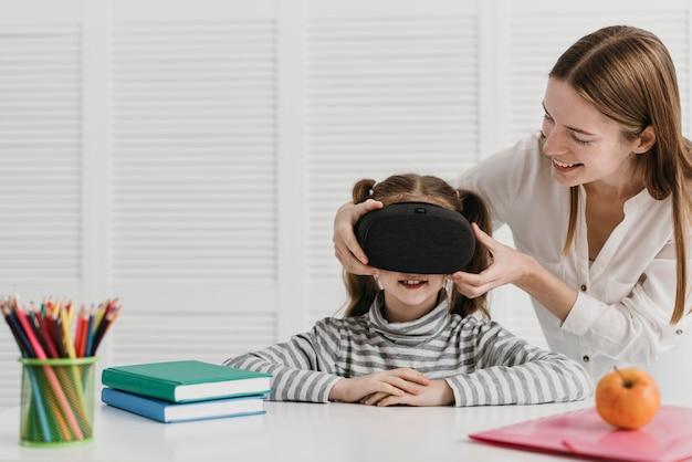 Matka i dziecko korzystające z zestawu słuchawkowego wirtualnej rzeczywistości w domu