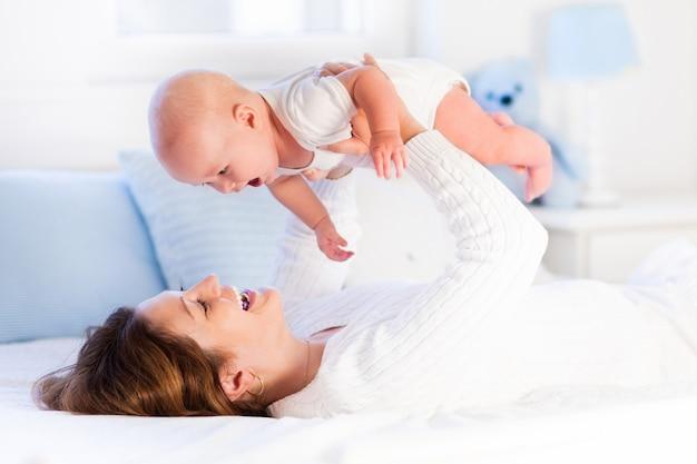 Matka i dziecko na białym łóżku