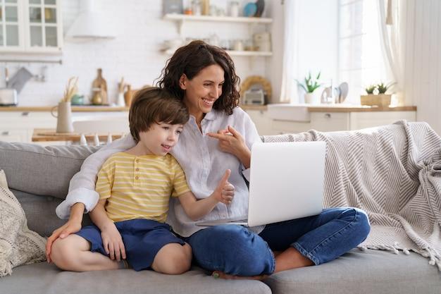 Matka i dziecko patrząc na laptopa z kamerą internetową do połączenia wideo
