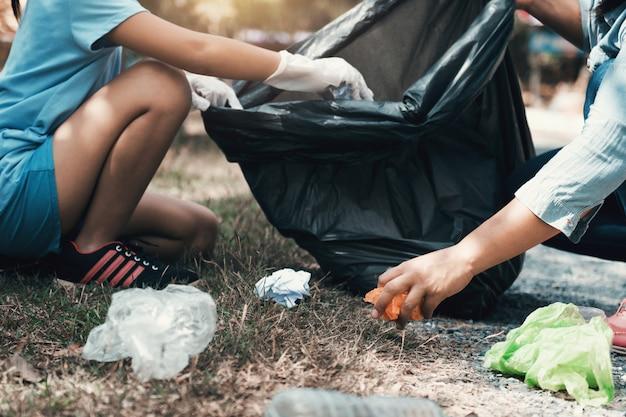 Matka i dziecko pomagają w zbieraniu śmieci w parku