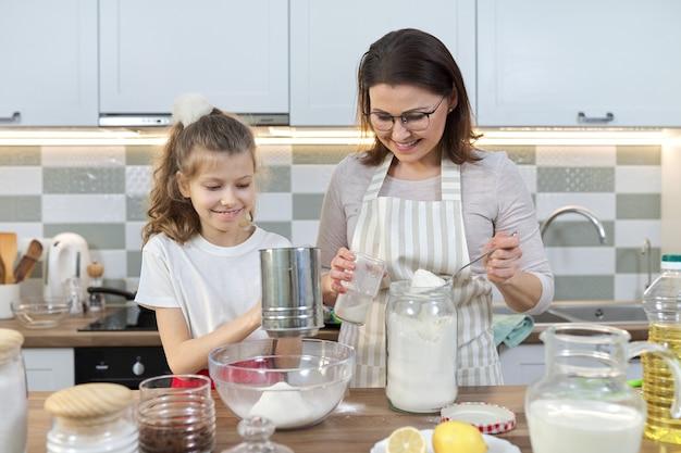 Matka i dziecko razem przygotowuje piekarnię w domowej kuchni. kobieta przesiewa mąkę, uczy córeczkę gotować babeczki. domowe jedzenie, rodzina, komunikacja z rodzicem i dzieckiem