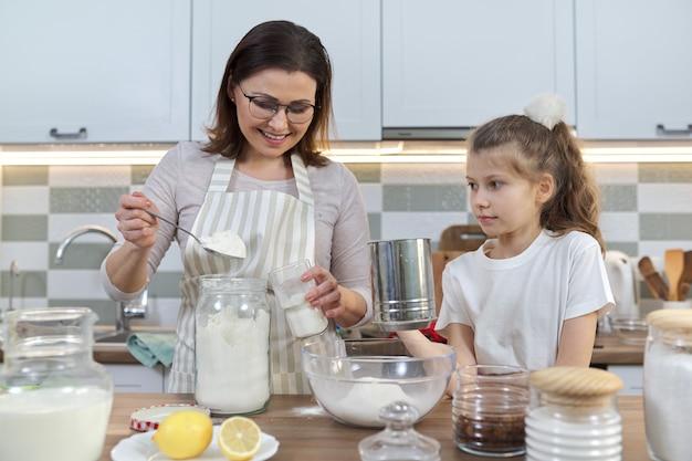 Matka i dziecko razem przygotowuje piekarnię w domowej kuchni