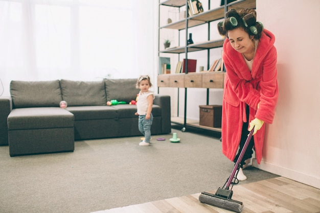 Matka i dziecko razem zaangażowane w prace domowe. ona myje podłogę mopa. gospodyni domowa i dziecko odrabiania lekcji. kobieta z małym dzieckiem w żywym pokoju. gospodyni domowa wykonuje wiele zadań podczas patrzenia