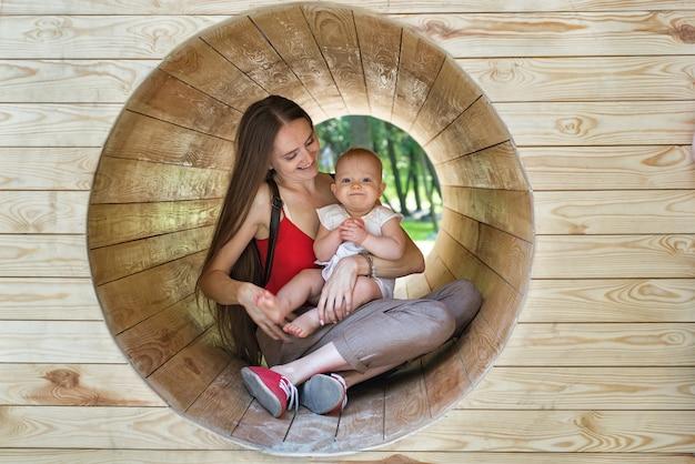 Matka i dziecko siedzą w drewnianym tunelu na placu zabaw. szczęśliwa mama i dziecko