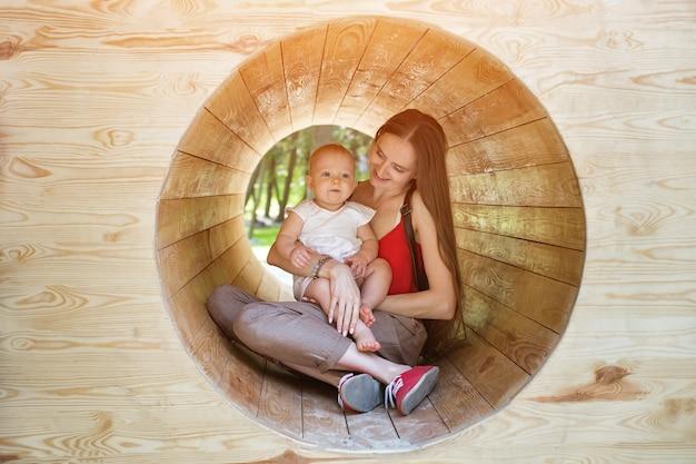 Matka i dziecko siedzi w drewnianym tunelu. ekologiczny plac zabaw.