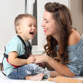 Matka i dziecko śmieją się podczas przygotowywania ciasta w kuchni