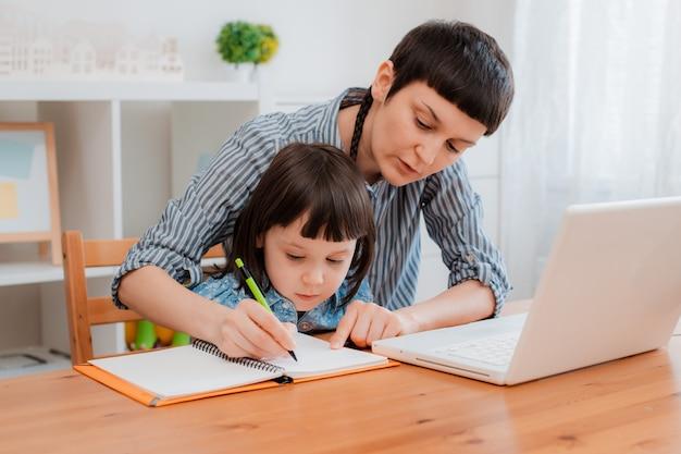 Matka i dziecko uczeń szkoły w domu na laptopie uczący się odrabiania prac domowych ehome schooling w okresie pandemii i koronawirusa