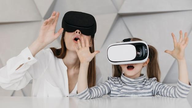 Matka i dziecko używają zestawu słuchawkowego do wirtualnej rzeczywistości i są zdumieni