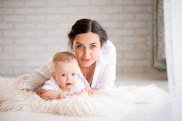 Matka i dziecko w białym pokoju. mama i dziecko chłopca w pieluchy pla