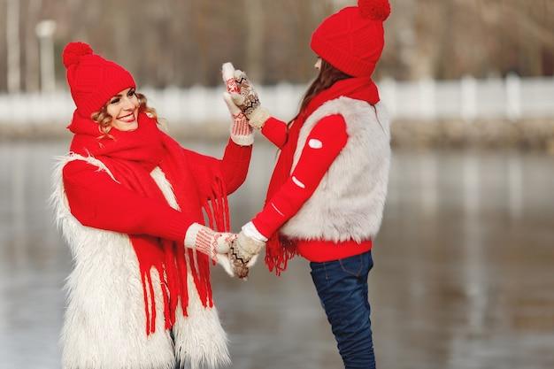 Matka i dziecko w czapki zimowe z dzianiny na rodzinne wakacje świąteczne. ręcznie robiona wełniana czapka i szalik dla mamy i dziecka. dziewiarskie dla dzieci. dzianinowa odzież wierzchnia. kobieta i mała dziewczynka w parku.