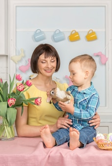 Matka i dziecko w wielkanocnej urządzonej pastelowej kuchni.