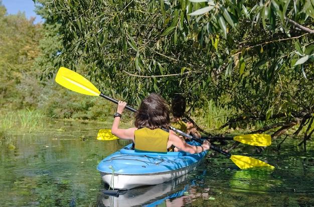 Matka i dziecko wiosłują kajakiem na wycieczce kajakiem po rzece