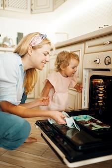 Matka i dziecko wyjmują z blachy do pieczenia piekarnika