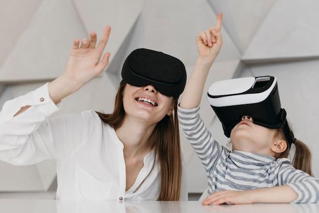 Matka i dziecko za pomocą zestawu słuchawkowego wirtualnej rzeczywistości i skierowanej w górę