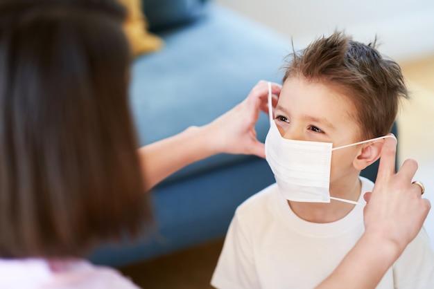 Matka i dziecko zakładają maski ochronne podczas pandemii koronawirusa