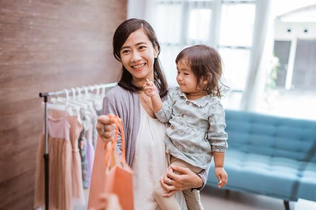 Matka i dziecko zakupy w centrum handlowym kupując ubrania. szczęśliwa mama i córka w sklepie