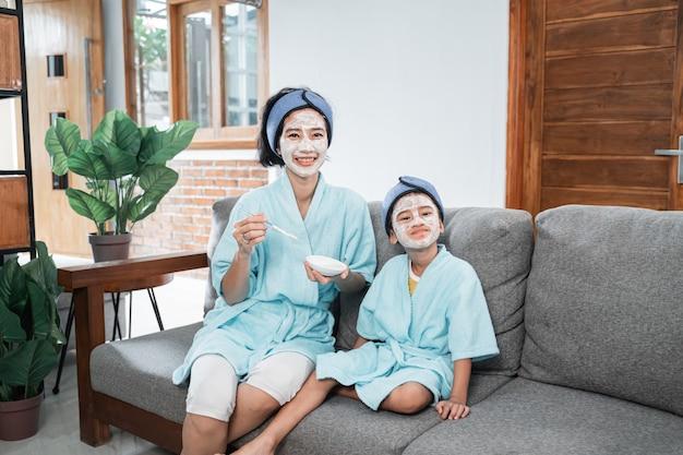 Matka i dziewczynka ubrana w kimono podczas robienia masek na twarz podczas relaksu w domu
