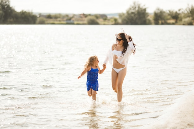 Matka i jej córeczka bawią się na wybrzeżu. młoda ładna mama i jej dziecko bawiące się w pobliżu wody