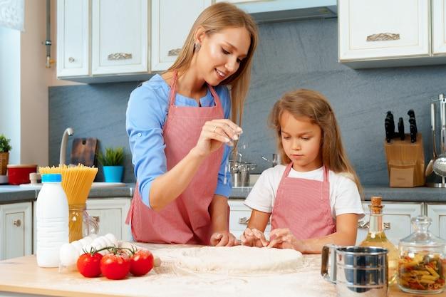 Matka i jej córeczka przygotowują ciasto w kuchni