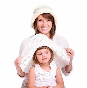 Matka i jej córeczka w kapeluszach na białym tle