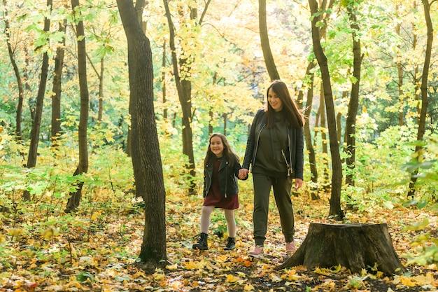 Matka i jej córeczka w parku jesień w sezonie jesiennym.