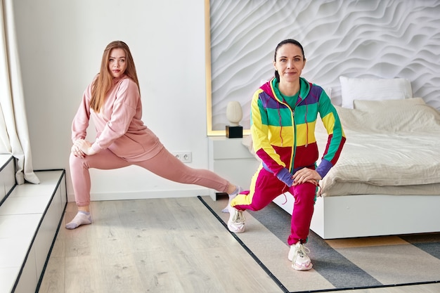 Matka i jej córka robią ćwiczenia rozciągające