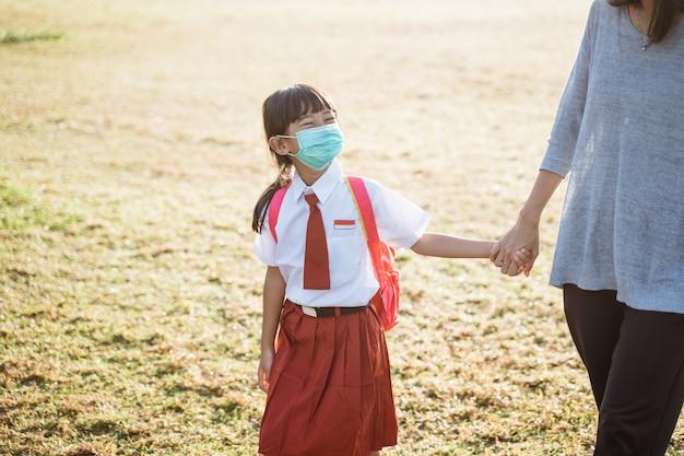 Matka i jej córka spacerują razem i noszą maskę na twarz