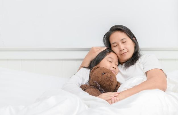 Matka i jej córka śpią na łóżku