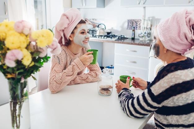 Matka i jej dorosła córka piją herbatę z maseczkami na twarz. kobiety chłodzące i rozmawiające w kuchni