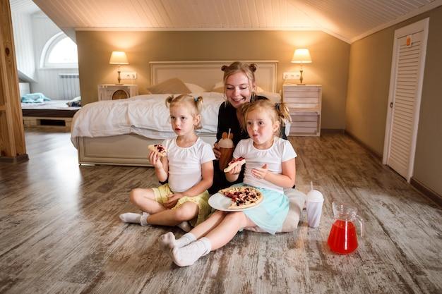 Matka i jej dwie córki oglądają telewizję i jedzą pizzę, piją sok.