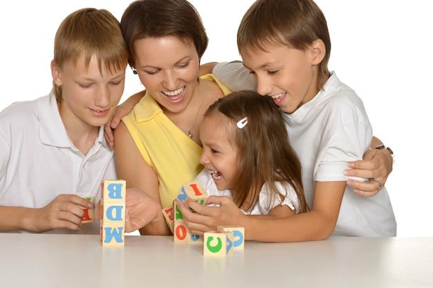 Matka i jej dzieci bawiące się kostkami na białym tle