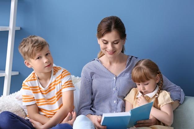 Matka i jej dzieci czytają razem książkę w domu