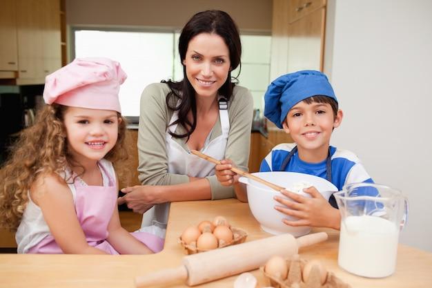 Matka i jej dzieci przygotowuje ciasto