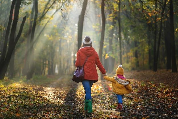 Matka i jej dziecko na wallk przy jesień lasem. widok z tyłu