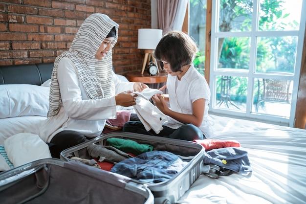 Matka i jej dziecko przygotowują ubrania i wkładają walizkę do noszenia, gdy mudik
